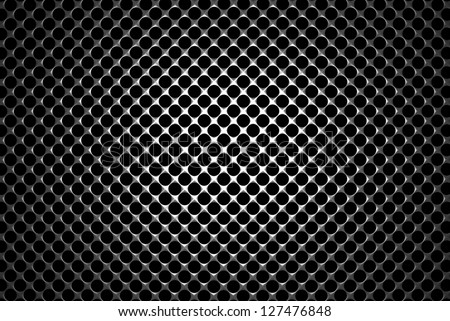 Steel grid with round holes and reflection on black background under the round central light, abstract textured background