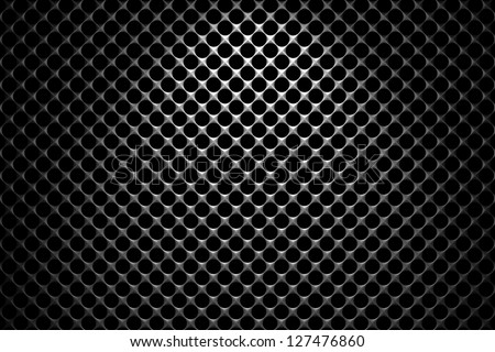 Steel grid with round holes and reflection on black background under the spot light, abstract textured background