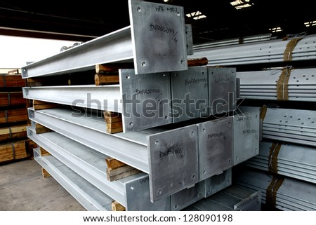 Steel H-beam bunch on the rack in warehouse - stock photo