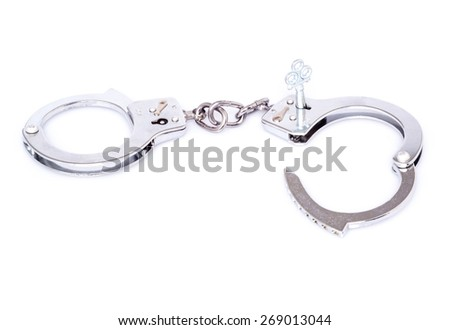 Steel handcuffs isolated on white background - a decorative key is inserted into one half which is partly open - stock photo