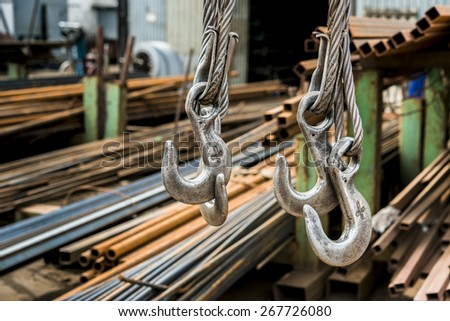 Steel hooks hang on the background of rolled metal products factory warehouse - stock photo