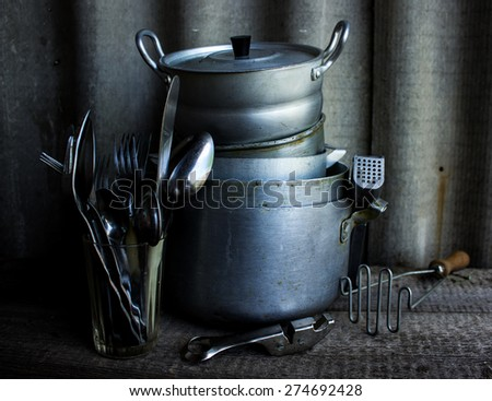 steel kitchenware on table, on wooden background - stock photo