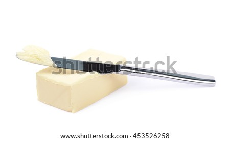 Steel knife over a briquette piece of a butter, composition isolated over the white background - stock photo