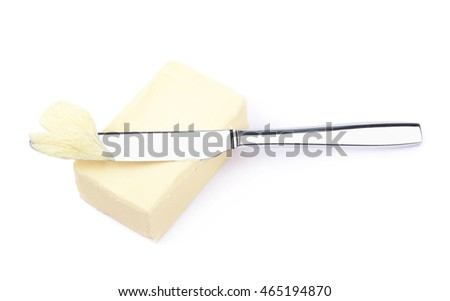 Steel knife over a briquette piece of a butter, composition isolated over the white background