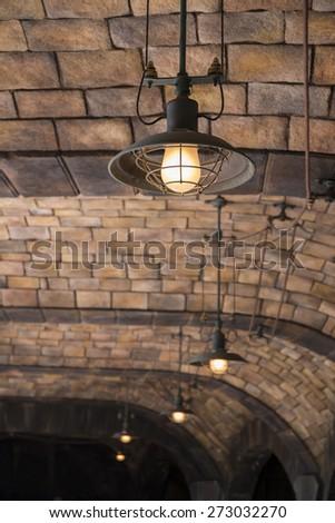 steel lamp under brick ceiling of the bridge - stock photo