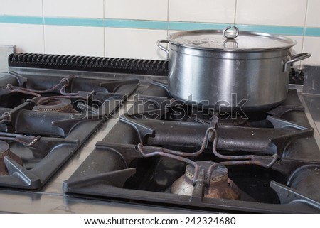 steel large pot over the stove of industrial kitchen - stock photo