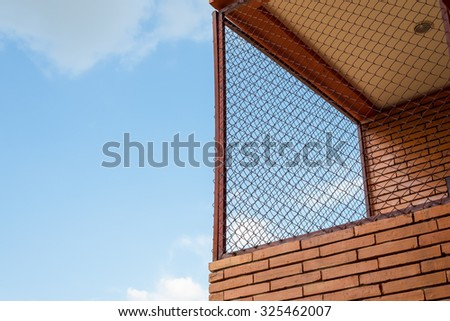 steel mesh at balcony with brown brick wall and blue sky