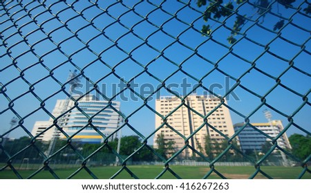 Steel mesh fence on blur stadium background.