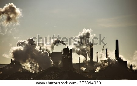 Steel-mill plant scenery line with fuming chimney-stalks in Hamilton Ontario