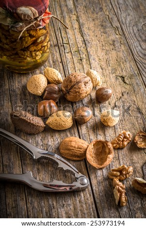 steel nutcracker and nuts of various kinds, nuts in honey - stock photo