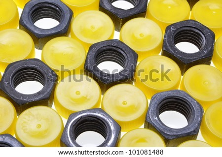 Steel nuts and plastic caps abstract summary - stock photo