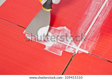 steel pallet fill up joints between ceramic tiles whit grout - stock photo