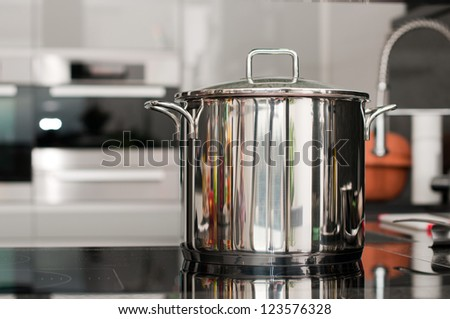 Steel pan on a hot plate in the kitchen - stock photo