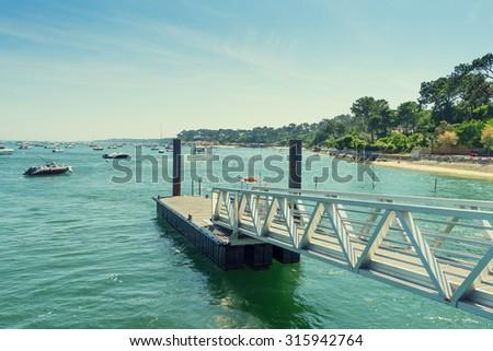 steel pier near seashore, ships and boats float in the sea - stock photo