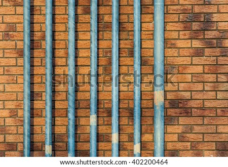 steel pipes in front of red brick wall background