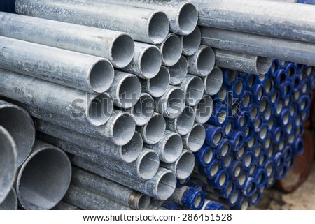 Steel pipes stacked in warehouse site - stock photo