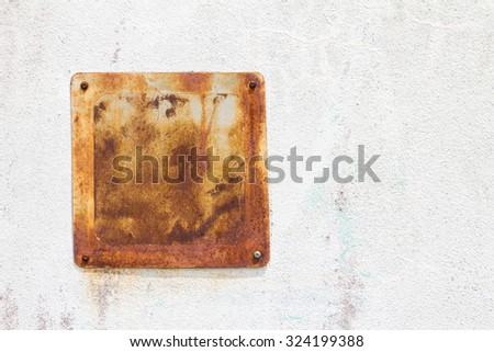 Steel plate, small square where the old weathered rust attached to the white concrete wall. - stock photo