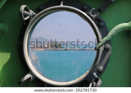 Steel porthole of warship - stock photo