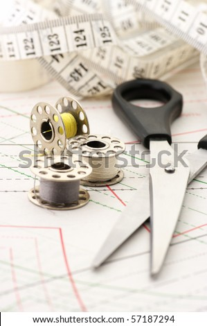Steel scissors with black handle, spools of thread and tape measure on paper sewing pattern. - stock photo