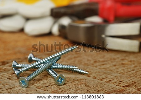 steel screws and different tools on  wooden background.