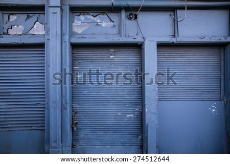 Steel shipping doors on blue building  - stock photo