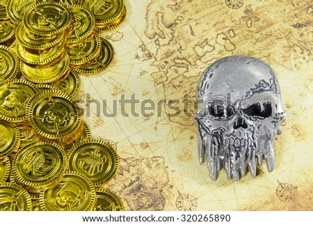 steel skull and pirate golden coin on a old world map - stock photo