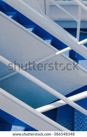 Steel staircase on a ship with blue stairs and white handrails; Ship building industry; Upstairs and downstairs - stock photo