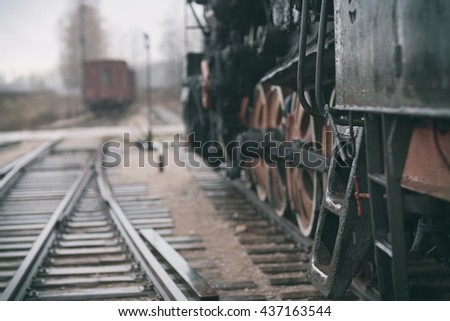 Steel stairs in Vintage steam train on wet rails of the railway station on a cloudy day with rain - stock photo