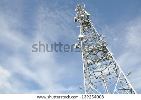 Steel telecommunication tower with antennas over blue sky