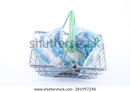 Steel wire shopping basket full of euros stacks. Isolated on a white background - stock photo