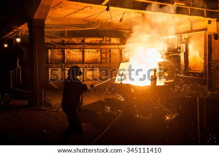 Steelworker when pouring liquid titanium slag from arc furnace - stock photo