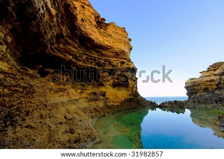 Steep cliff and calm water with reflections