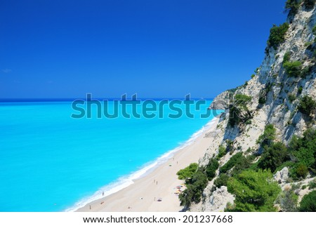 Steep cliffs and large long beach with turquoise sea on the island of Lefkada in Greece - stock photo