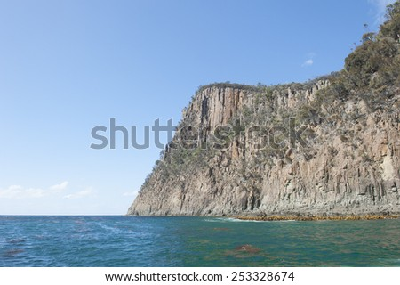 Steep high rocky cliff coast at Bruny Island, Tasmania, Australia, popular tourist destination, with view over Southern Ocean to horizon, blue sky as copy space. - stock photo