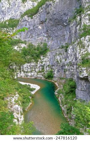 Steep limestone walls above narrow river at the bottom of a canyon, Montenegro - stock photo