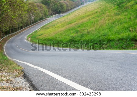 Steep road. Reduce speed and use a lower gear. Drive with caution. - stock photo