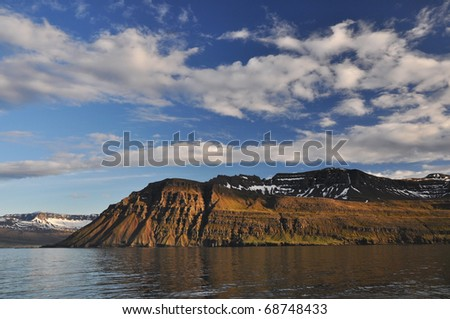 Steep rocky fjord and beautiful sky, East fjords Iceland - stock photo
