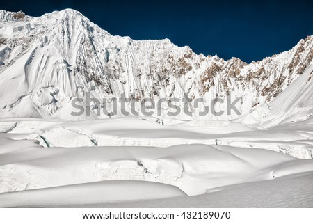 Steep slopes of Karakorum mountains and huge crevasses of South Gasherbrum Glacier - stock photo