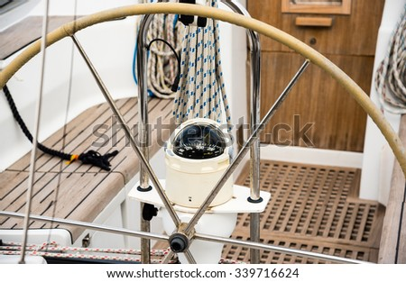 steering wheel and compass on a sailing boat - stock photo