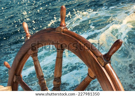 Steering wheel at sea background.  Skipper's wheel on an old ship. - stock photo