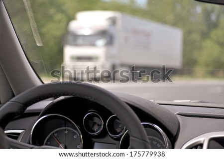 Steering wheel of a car while driving with truck in background - stock photo