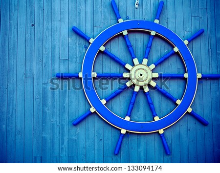 Steering wheel of the ship on a wooden wall of restaurant in marina - stock photo