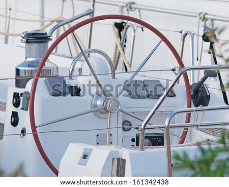 steering wheel on a white boat - stock photo