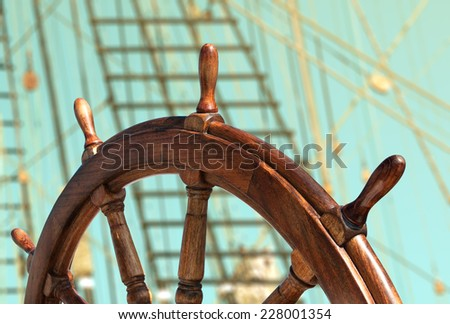 Steering wheel on the old ship. Nautical adventure of the ancient sailing vessel. Travel background with a wooden helm closeup. Ship wheel on the old sailing vessel - nautical equipment. - stock photo
