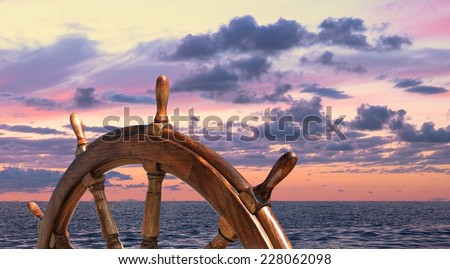 Steering wheel on the ship at sunset background. Skipper's wheel on an old ship. Ship rudder on the yacht, side view. - stock photo