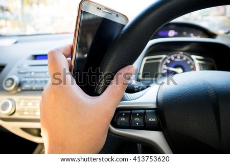 steering with hand holding mobile phone - stock photo