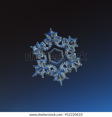 Stellar dendrite snowflake, glowing on dark blue background. This is macro photo of real snow crystal with relief arms and flat central hexagon, captured on glass surface with LED back light.