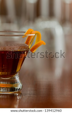 stemless martini glass with an orange liquor served on a busy bar top garnished with an orange twist - stock photo