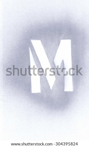 Stencil letter M sprayed with silver spray paint on white paper - stock photo