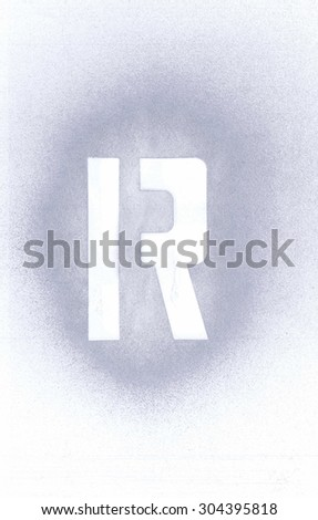 Stencil letter R sprayed with silver spray paint on white paper - stock photo